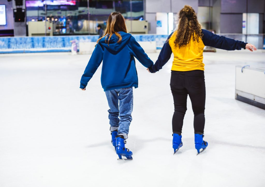 two people skate on an ice rink